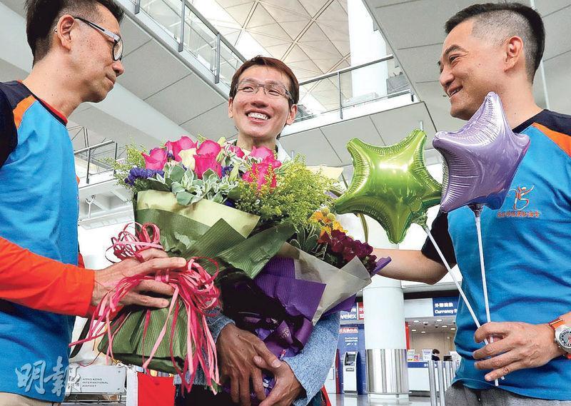 吳俊霆(中)昨與兩名成功攀到珠峰大本營的換腎康復者陳國明(左)及黃炎華(右)返抵香港,3人獲接機親友送贈鮮花及心意卡祝賀。(李紹昌攝)