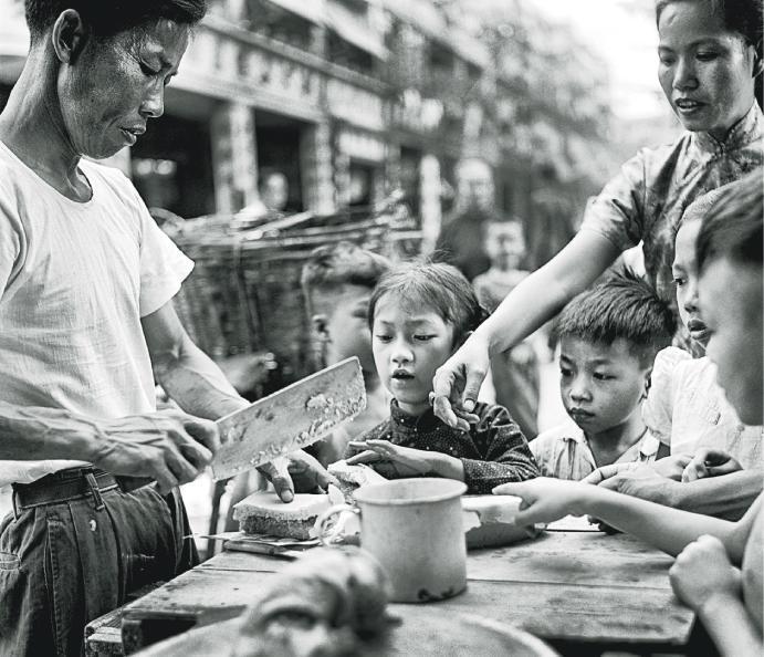 何藩嘅《念香港人的舊》載有多張舊香港照片,其中呢張《貪嘴》記錄咗當時嘅細路仔圍住嘢食檔嘅一刻。(照片由藍蓮畫廊提供)