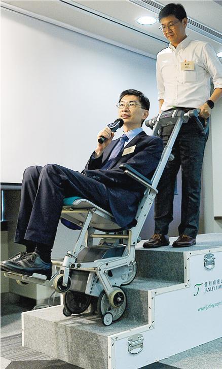 政府與社聯合辦的長者科技產品展覽將於明日開幕,社聯總裁蔡海偉(左)日前在另一活動上,親身示範協助行動不便長者上落樓梯的最新設備。(資料圖片)