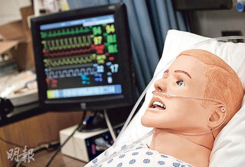 機械模擬病人可透過電腦程式控制,模擬不同病况,訓練學生以正確方法應對。圖為港大護理學院現有的模擬病人,旁邊屏幕顯示其維生指數。(港大提供圖片)