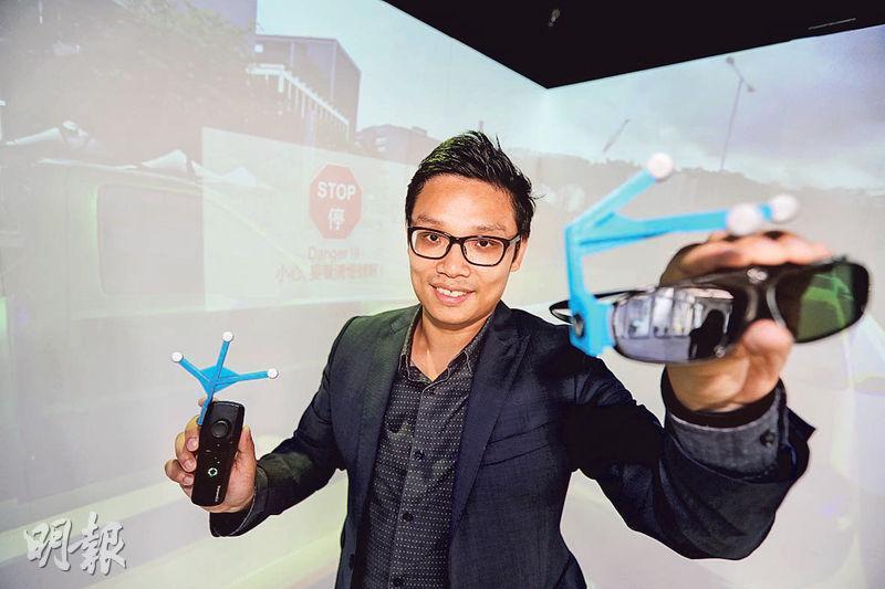 VirCube首席執行官及首席技術官曾俊雄表示,相比一般VR平台的眼鏡,其公司開發的系統只需配置他手上較輕盈的眼鏡,眼鏡上藍色部分為追蹤器,追蹤器上的灰色小圓球是反射物料,令用家與VR平台互相連接。他說系統可讓用家自行設計虛擬世界內容,已獲兩所中學購入作教學用途。(郭慶輝攝)