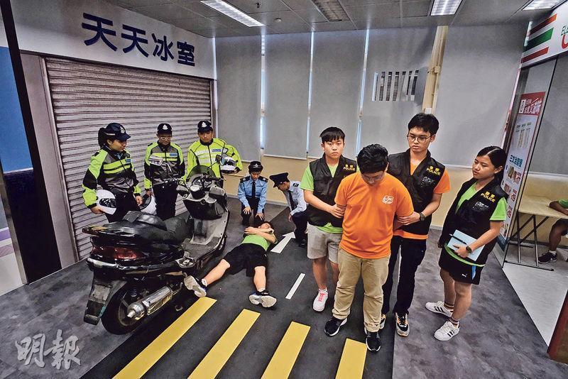 少訊中心內有模擬罪案現場訓練室,模擬場景包括港鐵車廂、茶餐廳、單位等,參加者可模擬以警察身分處理事故,如圖中參加者扮演交通警員、傷者及刑事偵緝警員,讓他們更了解警方工作的程序。(蘇智鑫攝)