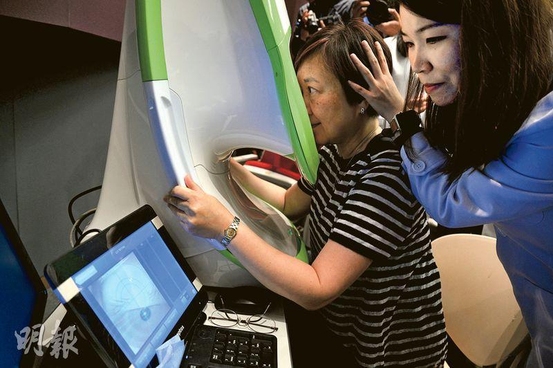 中大醫學院即日起招募100名參加者進行「早期阿茲海默症篩查研究」,參加者要接受視網膜影像掃描及血液測試等。市民謝太(左)試用「超廣角視網膜掃描機」,檢查視網膜血管及毛細血管網絡的健康情况,此檢查不具入侵性,一般可於半小時內完成。(蘇智鑫攝)