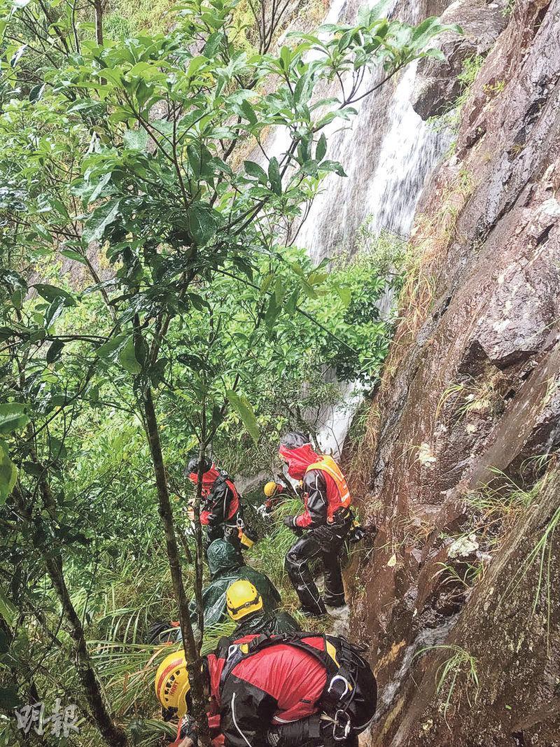 消防高空拯救專隊在8月27日被派到飛鵝山拯救兩名被困行山客。專隊接到Mayday求救信號後,共派出30名隊員到場,先徒步沿百花林走至山肩位置,再滑落傷者停留的懸崖(圖)。(圖﹕消防處提供)