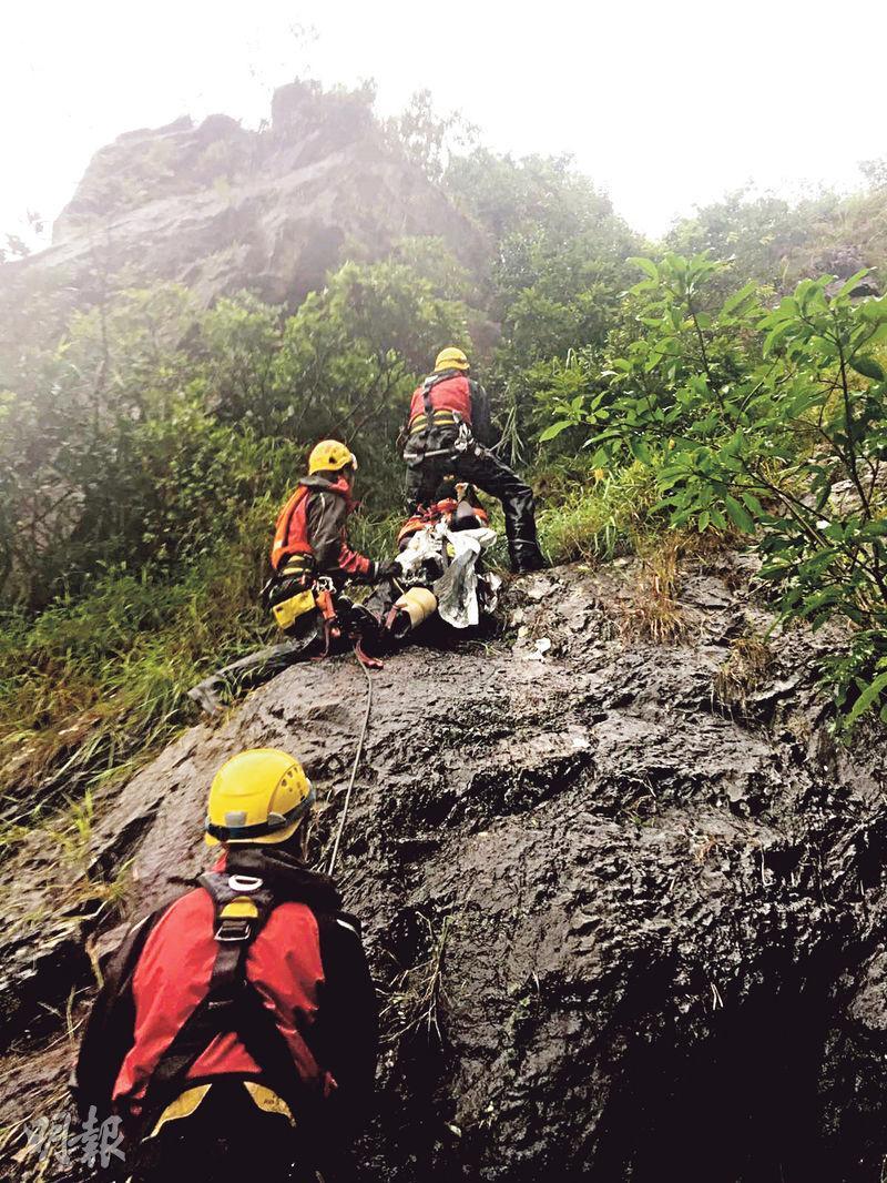 專隊將兩傷者送走,女傷者被置於抬牀上,由專隊游繩將她拉上陡峭懸崖,再送到較平坦山路(圖)。專隊亦以繩索將男求救者綁緊,助他離開現場。(圖﹕消防處提供)