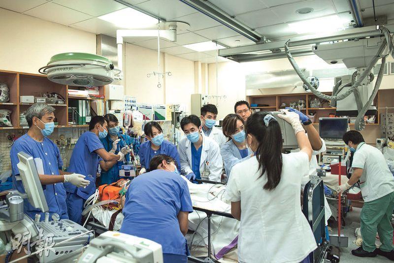 瑪麗醫院逾20名醫護人員爭分奪秒搶救車禍傷者伍潤庭,當時一眾醫護全神貫注望着儀器,監察伍的生命迹象指數。瑪麗醫院成人深切治療部副顧問醫生蔡雅穎憶述,當日不知有攝影記者在場,事後看到照片,發現圖右有醫院清潔工在打掃,為每個人都在不同崗位付出而感動。(瑪麗醫院提供)