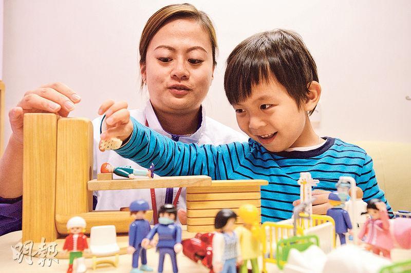 兒童癌病基金專業服務副經理梁藹琳(左)負責跟進腦癌男童然仔(右)的療程,以積木模型向然仔解釋電療過程。(楊柏賢攝)