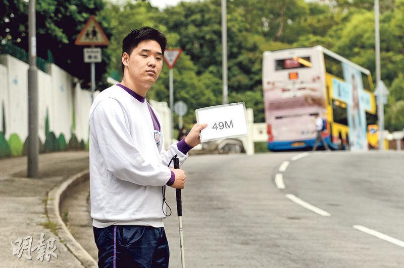司徒華獎得獎者楊恩華視力只有常人一成,平日搭小巴上學需要舉號碼牌,令司機知道他要上車。他說平日同學和司機都會協助他上車,令他很感動。(楊柏賢攝)