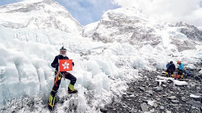 本身任職物理治療師的吳俊霆,5月攀上珠穆朗瑪峰之巔。圖為他手持區旗在大本營冰壁旁拍照留念。(資料圖片)