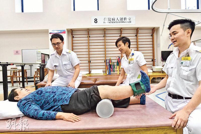 馮太(藍衣者)示範在家中如果用奶粉罐做強化四頭肌的復康運動,她說在家可參考此動作的短片,以準確地做好伸展範圍。右一為東區醫院一級物理治療師文鎮邦。(馮凱健攝)