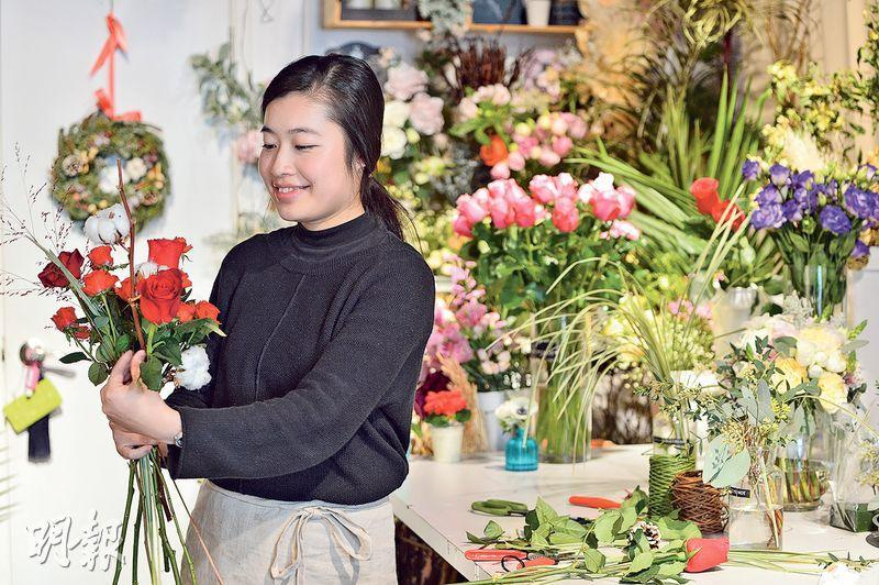 Miranda(圖)製作手上花束時,用上大小不一的紅玫瑰和近年韓國十分流行的棉花。她計劃年宵時推出劍蘭、百合等傳統年花,將加入花藝元素,創造出不失傳統,但讓人耳目一新的花束。(鄧宗弘攝)