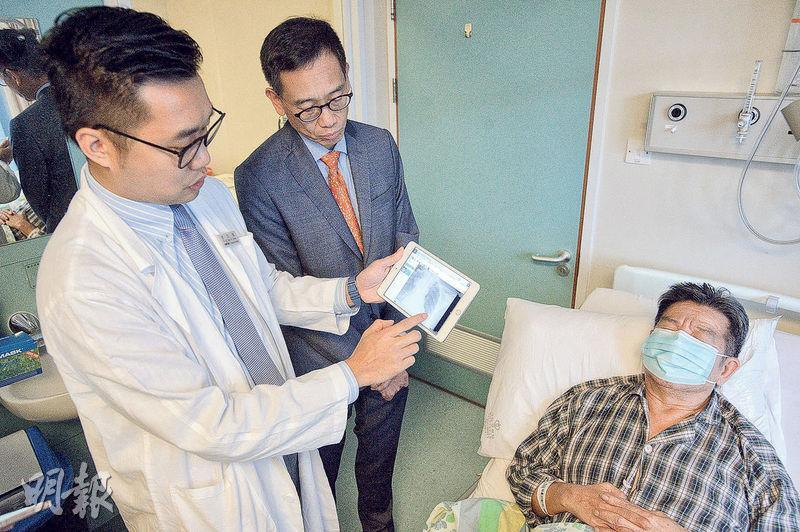 將軍澳醫院外科醫生李文傑(左一)表示,醫生巡房時可用平板電腦向病人展示X光片,影像在裝置上可放大縮小、調校光暗度等,增強醫患溝通。旁為醫管局資訊科技及醫療信息主管張毅翔(左二)。(楊柏賢攝)