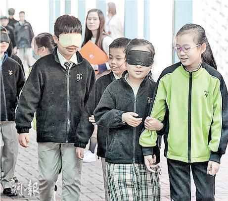 小學生戴上眼罩體驗漆黑世界,並由同伴引領向前走。(政府新聞網相片)