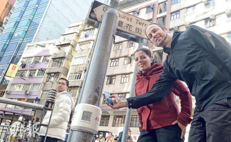 來港5年的夫婦Matthew(右一)和Marta(右二)為荷李活道的燈柱設計智慧路標,配上彩色圖案,代表美食、文化、藝術和歷史古蹟四大主題。旅客用手機掃一掃燈柱下方的QR Code,可連結至該智慧路標代表的主題,得悉中環相關的好去處,令燈柱變身導遊。(劉焌陶攝)