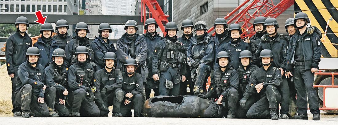 警方爆炸品處理課人員昨拆彈後與炸彈合照,爆炸品處理課在行動中共出動15人,當中包括女將(箭嘴示)。(林智傑攝)