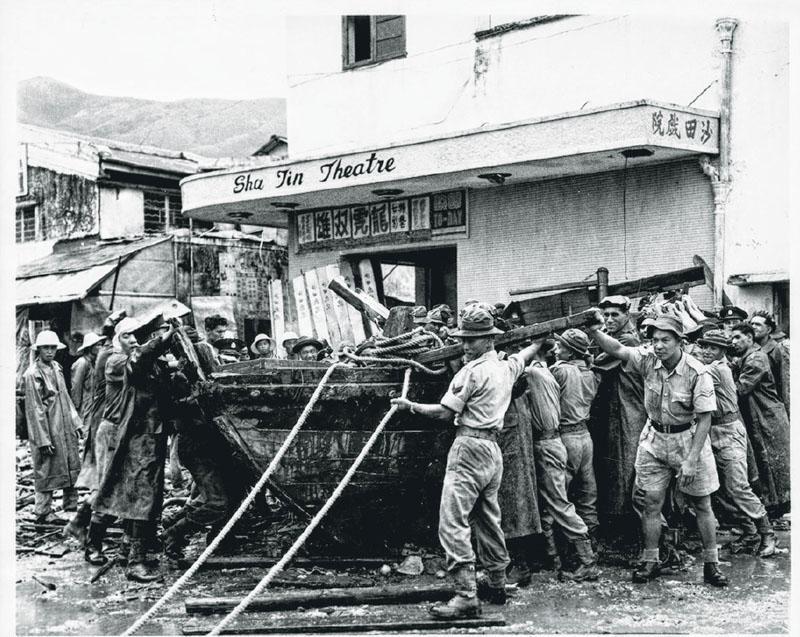 1962年超強颱風溫黛襲港後,一艘漁船被大浪冲上陸地,落在沙田戲院門外。(政府檔案處提供)