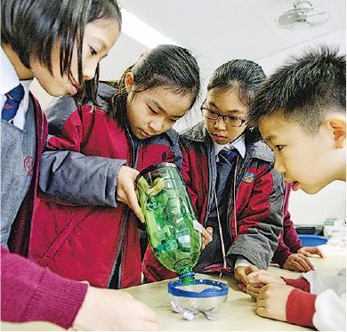 許多科學實驗充滿創意,圖為協和小學學生研發出來的吸塵機,他們正嘗試吸塵。(楊柏賢攝)