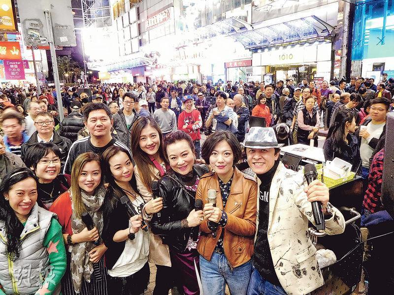 「旺角羅文歌舞團」是西洋菜街最多藝人的表演單位。圖為創辦人「旺角羅文」梁志源(右一)與龍婷(右二)、天天(右四)等部分合作藝人及粉絲合照。