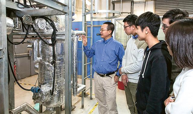 周文忠博士(左一)跟同學分享兩相流沸騰與凝結實驗裝置的研究成果。