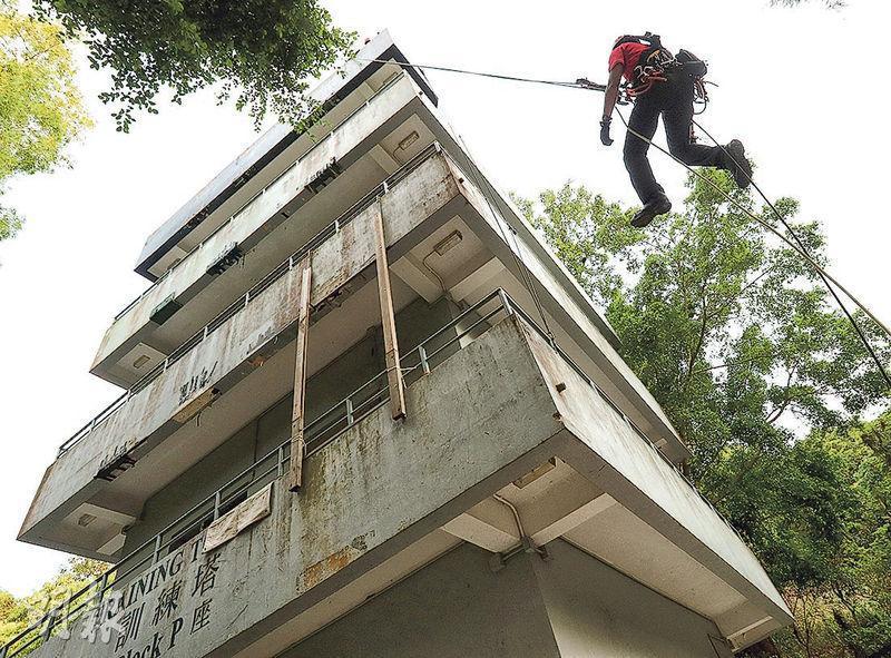 警察高空工作隊其中一項職責為將構成危險的物件移走,隊員須快速移往目標完成任務。昨日高空工作隊模擬有人高空擲物,隊員要「橫移介入」,從3樓游繩至1樓,由右邊牆身彈跳至左邊,再迅速關上窗,完成後彈回右邊牆身,整個過程在5秒鐘內完成。(李紹昌攝 )
