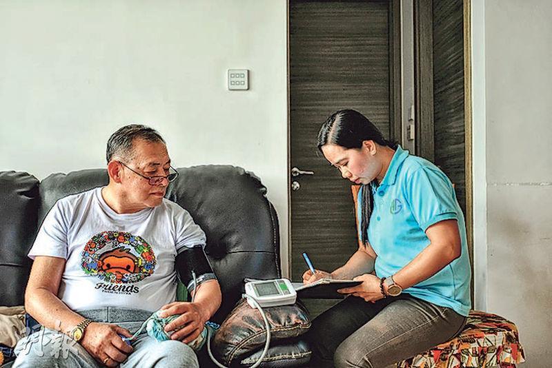 菲律賓護理員Caroline(右)平日會協助中風的長者許先生(左)量度血壓並作紀錄,以監察他的身體情况。她亦會帶領許先生做手腳運動,舒展筋骨,並協助他改善活動能力。(蘇智鑫攝)
