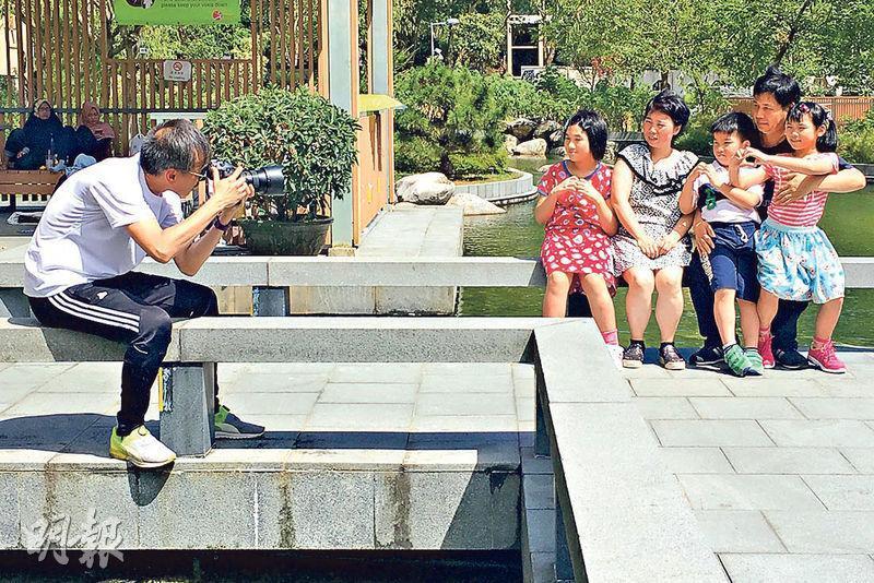 生命攝影師馬嘉健(左)噚日喺坑口文曲里公園,為基層家庭影全家福。(熊美芝攝)