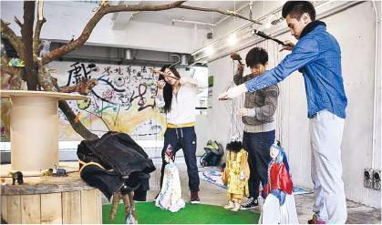 《水滸傳》戲偶——King(右)學習操縱提線木偶,手中的是《水滸傳》的林沖,中間黃衣木偶是魯智深。(圖:受訪者提供)