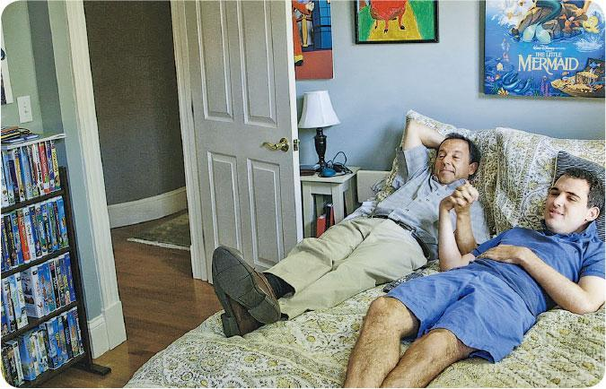 耐心溝通——父母陪伴Owen接受治療及學習,耐心嘗試不同溝通方法。搬屋收拾前Owen心情緊張,爸爸榮恩(左)陪他一起看小飛象動畫片。(圖:安樂影片)