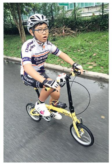 爸爸李家威本身愛好單車,約4年前於深圳看到一輛黃色小單車(圖中單車),感覺與自己的單車很相似,便買了帶回香港。兒子李泓樂(圖)果然很喜歡,並開始跟教練踩單車。李家威說,因跟隊練車是團體活動,而且有規律,泓樂不僅學懂與人相處,訓練完亦會自覺整理自己的單車。(受訪者提供)