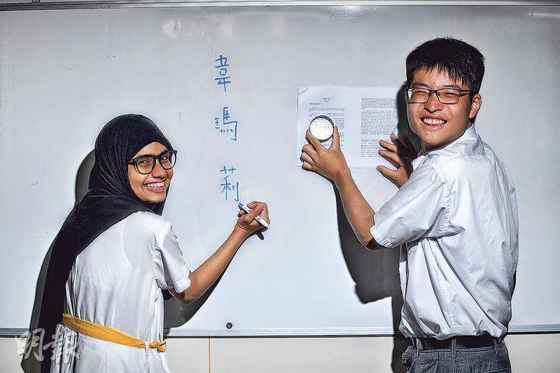 韋瑪莉(左)及謝翱駿(右)雖各自面對學習中文及視力上的挑戰,但兩人未有埋怨,更努力克服,獲得「正能量青年選舉」金獎。謝翱駿視力不佳,放大鏡是長伴他的工具。(楊柏賢攝)