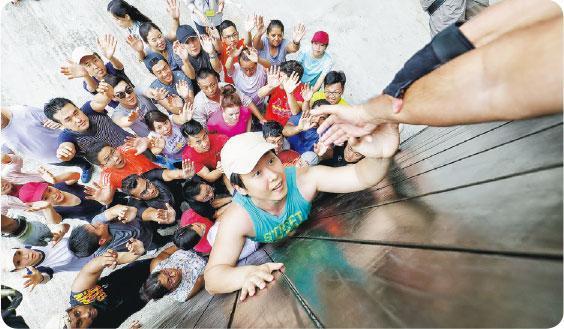 團隊合作——科大MBA課程中有項戶外活動,要求學生合作徒手攀上高牆,藉此訓練他們的團隊合作精神。(受訪者提供)
