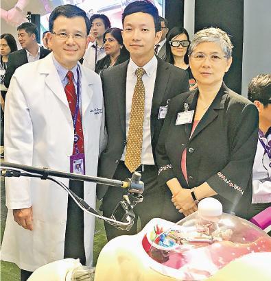 港大外科學系名譽臨牀教授兼香港無創外科有限公司創辦人楊重光(左),展示機械人外科手術系統的機械臂。港大婦產科學系系主任顏婉嫦(右)及港大普通外科專科醫生傅志聰(中)有份參與試驗。(李詠珊攝)