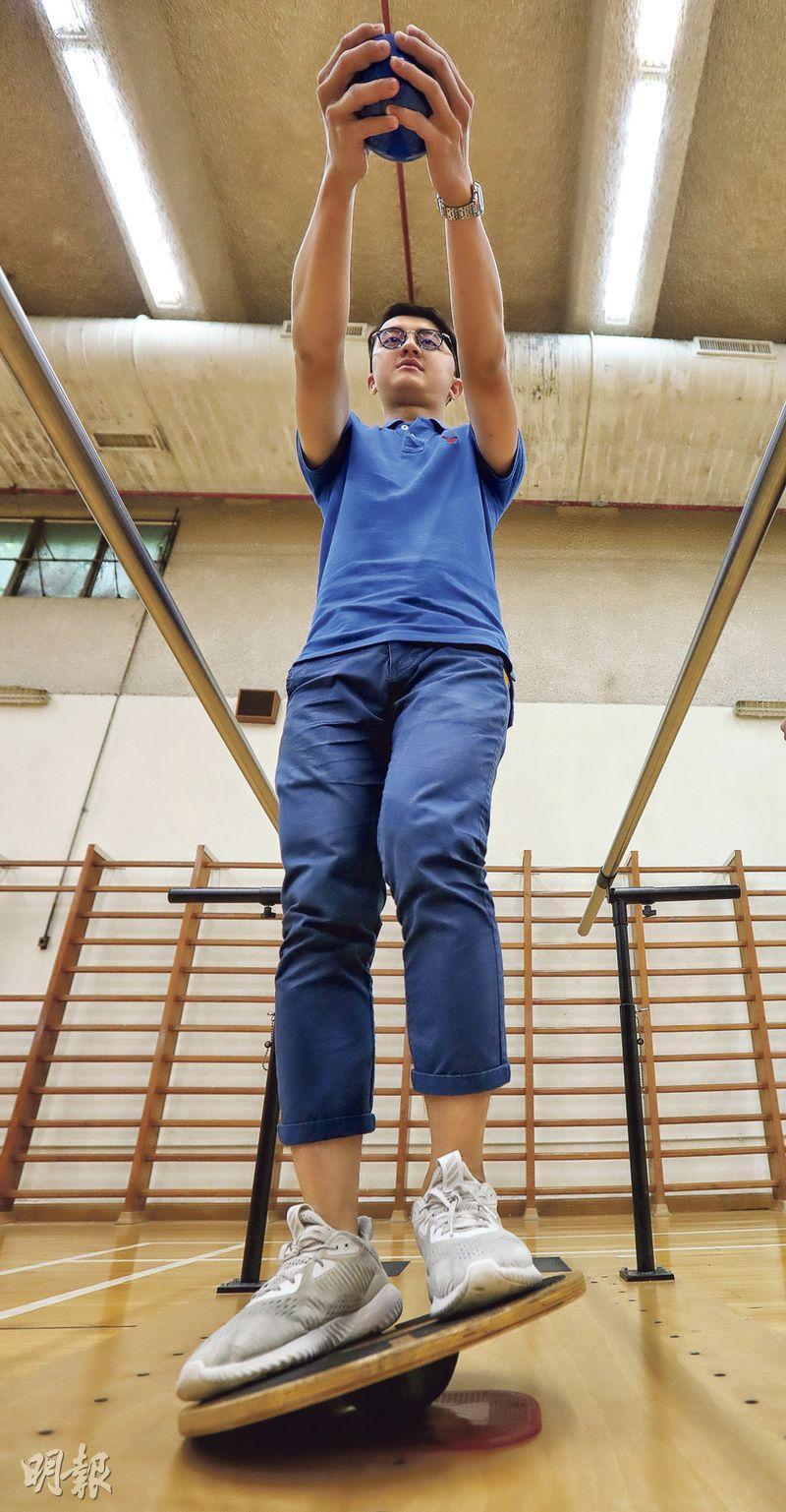 去年備戰馬拉松期間被的士撞至腦部重創的張允祈(圖),出院後在麥理浩復康院接受治療,現已恢復身體機能,可以跑步、打籃球等。圖為Ricky示範接受物理治療,該動作主要訓練平衡力、腹部和背部等肌肉。(李紹昌攝)