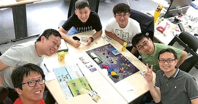 Nex Team Inc.聯合創始人、負責管理香港團隊的宋安來(左一)認為,需要為人才提供機會及發揮技能的空間,才可留住人才。他與另一聯合創始人陳穎鴻(左三)不時會和同事在香港辦公室進行消閒活動,如圖中正在玩桌上遊戲,工作氣氛融洽。(受訪者提供)