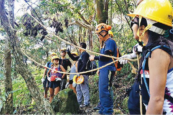 固定樹枝——黃龍坑郊遊徑內有不少斷樹,漁護署職員在評估鋸除風險後,先以繩索固定有可能跌下的樹枝,才出動電鋸開路。(受訪者提供)