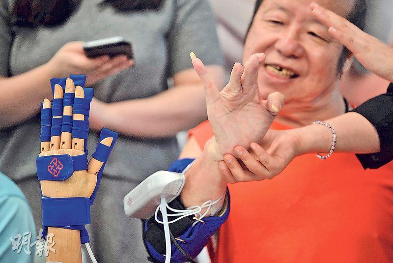 鄧先生(圖)去年第三度中風,出院後右手手指一直難伸展,現可通過手機程式操作理大新研發的機械臂,透過電刺激輔助,以及機械臂藍色手套部件(左)內的充氣組件外力輔助,手指彎曲伸展幅度大增。(鍾林枝攝)