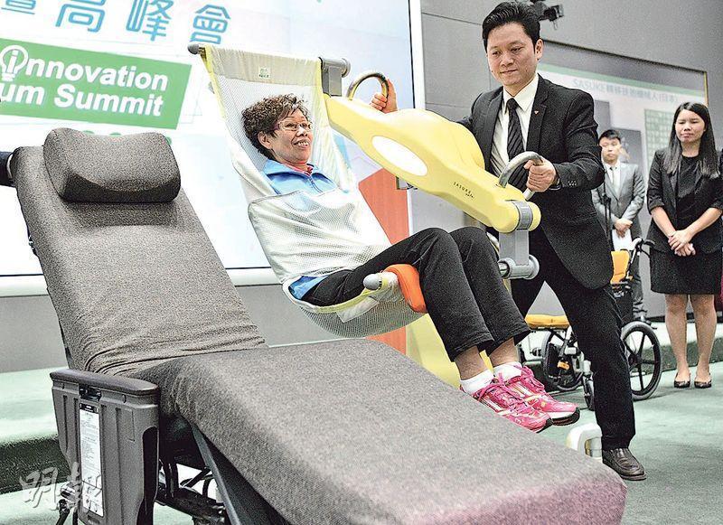 日本「Sasuke轉移扶抱機械人」(圖)現已用於當地不少安老院舍。職員先將保護單包着躺卧牀上的長者,機器會仿效雙手抱起姿勢,將長者慢慢升起,方便「過牀」移至輪椅等。(楊柏賢攝)