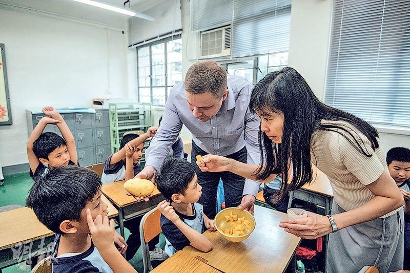 今學年有15間取錄智障學童的特殊學校設英國語文科。圖為屬輕度智障兒童學校的三水同鄉會劉本章學校英文課情况,該校授課加入大量感官元素,加強學生記憶。如科主任招鳳儀(圖右)及外籍英語教師在拍攝當天教授水果的英文,特意買來芒果讓學生品嘗。(馮凱鍵攝)