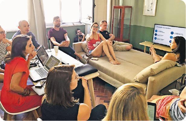 團友分享會——Olivia(沙發上右邊)與一班遙距工作旅行團的團友「放工」後自發舉行分享會,在住所的共用空間交流工作技能及業餘嗜好,好像回到大學的宿舍生活。(受訪者提供)
