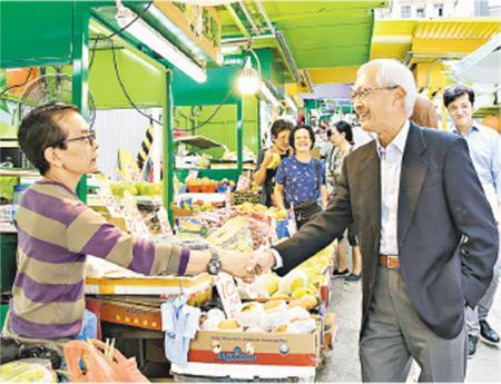 市建局主席蘇慶和(右)近日巡視中環嘉咸街露天街市,並探訪受火災影響的其中一檔檔主、「文記生果」老闆文業和。(市建局提供)