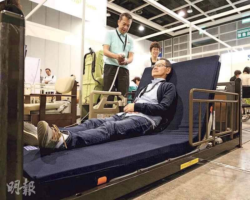 日本的「超低牀」(圖)可以電動升降,最低可降至離地7厘米,牀背亦可升高。FRANCEBED海外營業部長濱田浩美表示,不少腦退化的長者經常郁動或掙扎,有墮牀風險,把牀降低至接近地面,有助減低受傷風險。此外,不少院舍或因為想避免院友墮牀,將他們綁在牀上,惟做法影響長者身心,「超低牀」的設計理念是希望兼顧長者安全,同時讓他們有自主活動權。(曾憲宗攝)