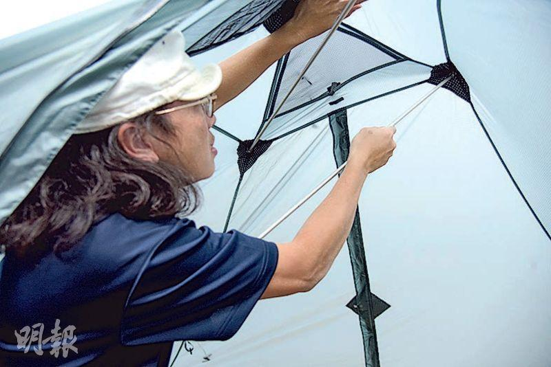 利用營釘將帳幕固定,避免帳幕在搭建過程中被風吹走。(黃志東攝)