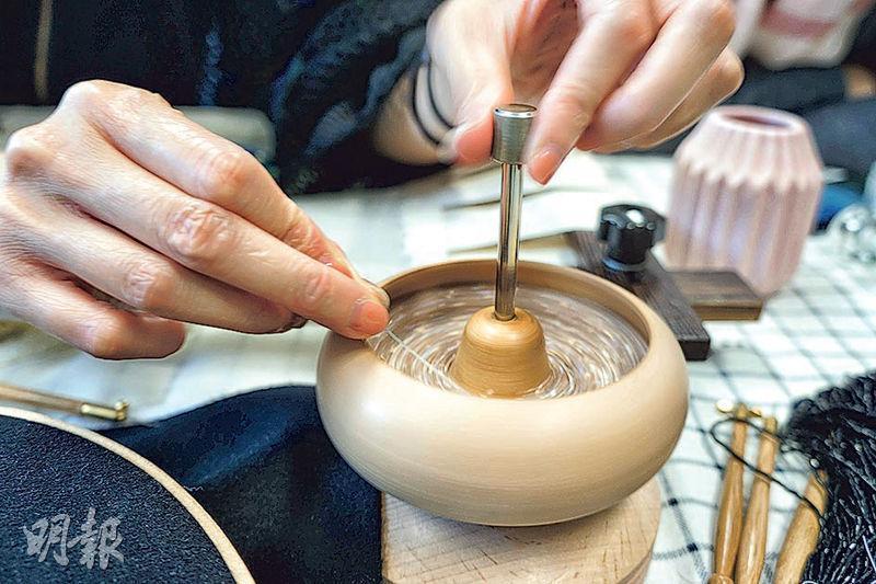 穿珠幫手——法式刺繡工具猶如法國人一樣貪靚,這個像極木頭小磨器的珠仔盤,又靚又會轉,自動把珠仔推進長針,一拉就是一串珠仔。(朱一心攝)