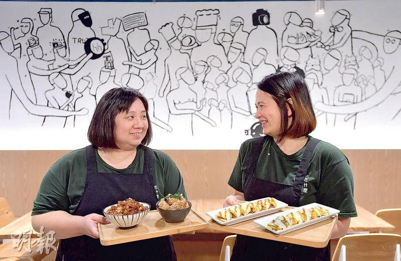 台灣媽媽Tracy(左)和Grace(右)去年捲入生意糾紛,今年在中環重新開店「吃什麼」,短短3個多月,昨重奪「車胎人美食推介」,Tracy形容這是一種肯定。新店一幅牆上畫滿她們遇到挫折時伸來援手的人,包括家人、熟客、不離不棄的員工,還有熱心的網民和記者。(鄧宗弘攝)