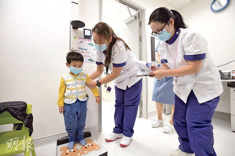 耗資130億元的香港兒童醫院昨正式啟用,首日有9名已預約的腎病兒童覆診。專科門診覆診流程包括度高、磅重、量血壓及見醫生等,圖為其中一名覆診的病童(左一)在醫護人員協助下度高。(楊柏賢攝)