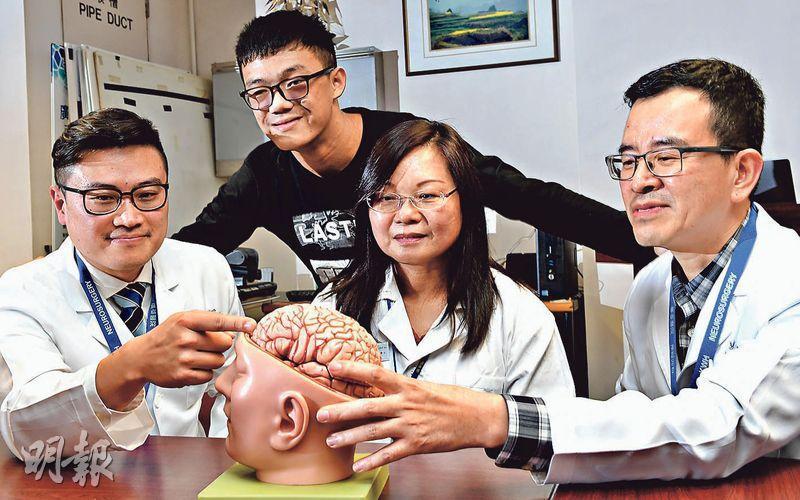 廣華醫院自2015年引入清醒開顱手術,最年輕的15歲病人Ben(後)在去年接受手術時邊聽歌邊玩雞玩偶,成功切除九成腫瘤,並保住了語言能力。廣華神經外科副顧問醫生胡日明(前左)認為,保持患者生活質素相當重要。前右及前中分別為神經外科副顧問醫生陳勇及臨牀心理科主管馬文嬌。(劉焌陶攝)