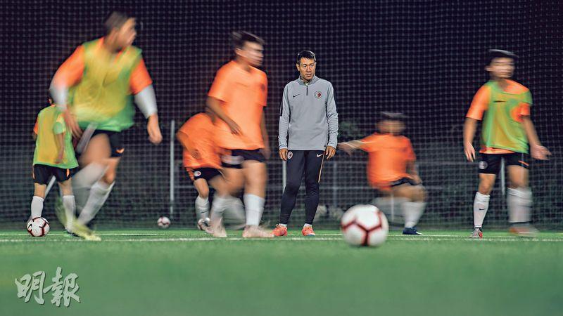郭嘉諾(中)為香港足球日以繼夜工作,即使晚上主持港足梯隊操練仍未言倦,聲音依舊鏗鏘有力。(馮凱鍵攝)