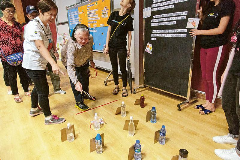 富泰會與不同的義工團體和機構合作舉辦多元化的活動,圖為院友和家人一起玩拋水樽遊戲考眼力。