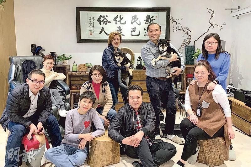 新達化工辦公室設置如同家居,有沙發、按摩椅,又有不少木頭和植物擺設,Terry(後排左二)和Edmond(後排右二)一周還會有三四天帶兩頭柴犬回公司。他們自豪道,公司流失率為0,員工向心力很強。(黃心悅攝)