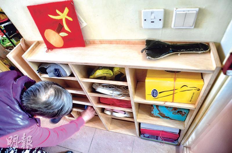 市建局與中大建築系學生合作,以書展的宣傳木板「升級再造」家具,按謝婆婆的需要度身訂做鞋櫃。婆婆收到後非常興奮,立即放上數雙鞋及雜物,整理一番。(劉焌陶攝)